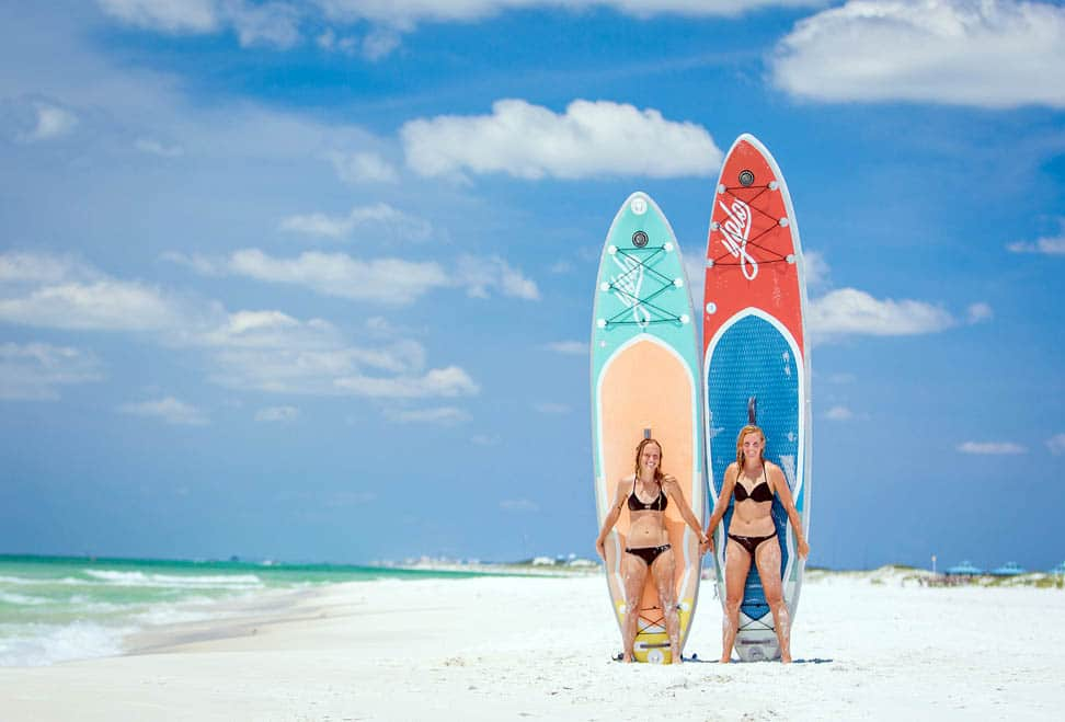 2 girls holding paddle boards on the beach of North Myrtle Beach